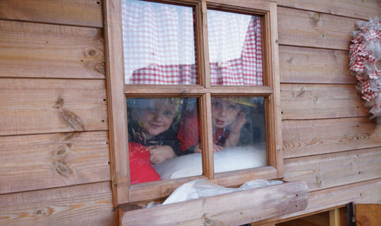 nursery facilities - children playing in the wendy house outside