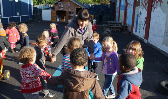 children playing with carers in the outside play area facility