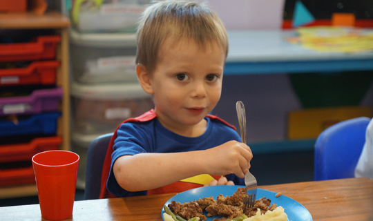 boy using his fork to eat cottage pie at nursery mealtime
