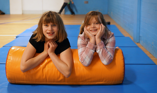 two young girls looking towards camera on soft play apparatus