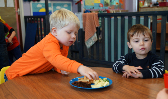 two boys sharing their nursery mealtime snack