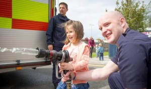 Child using fire hose with fireman